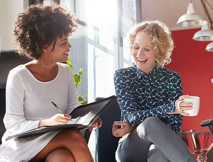 brendabyers.com - an image of coaching session with two women laughing - an African American woman with a clipboard and a blonde Caucasian holding a white coffee cup with a bright red wall